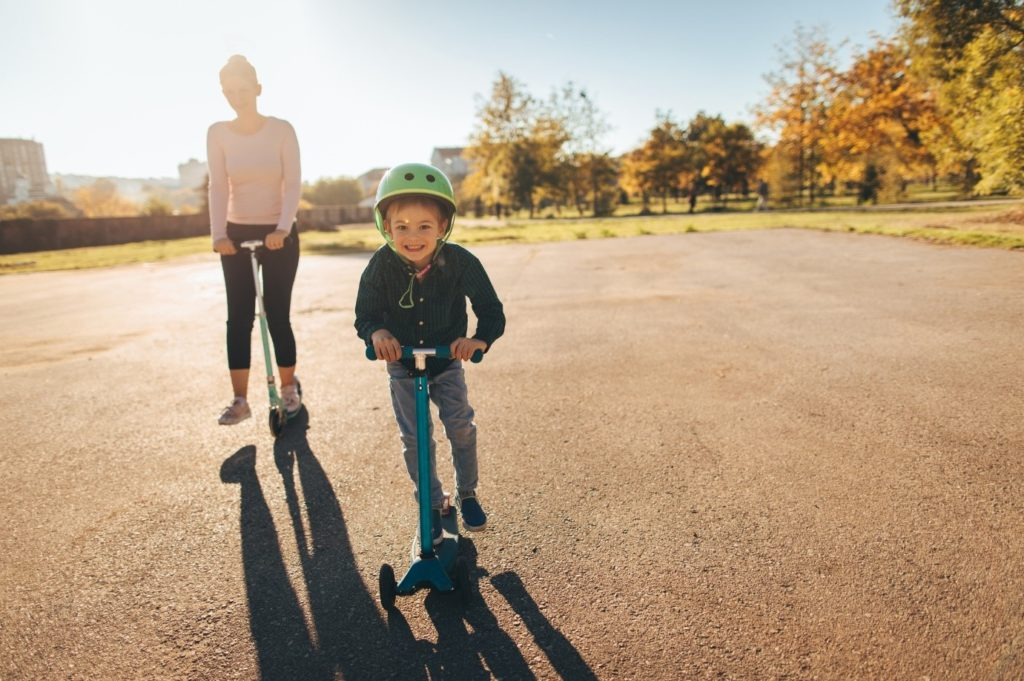 Image shows a small boy on a scooter moving towards the camera, smiling. His mother is also on a scooter, behind him. It is a sunny day.
