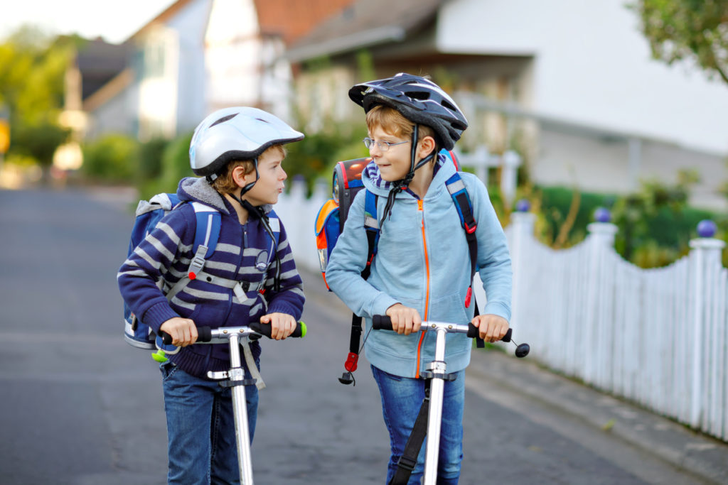 Two primary aged boys playing on their scooters.