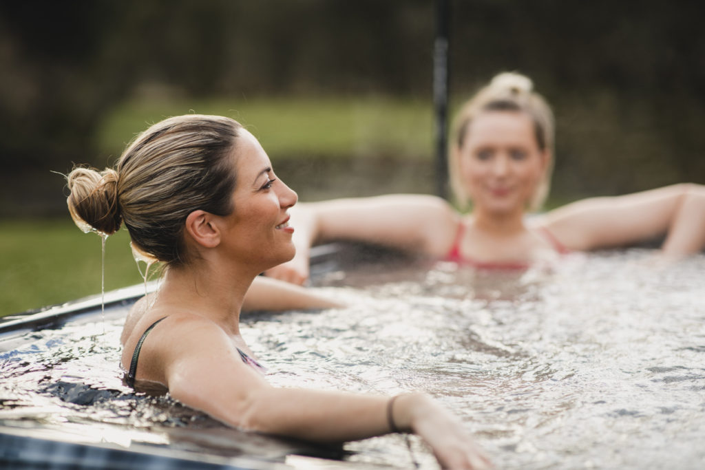 Two blonde ladies relaxing in a garden hot tub.