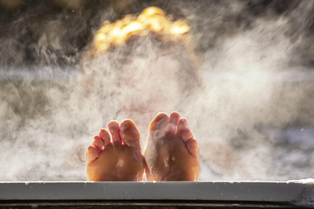 Feet poking out of a steaming hot tub.