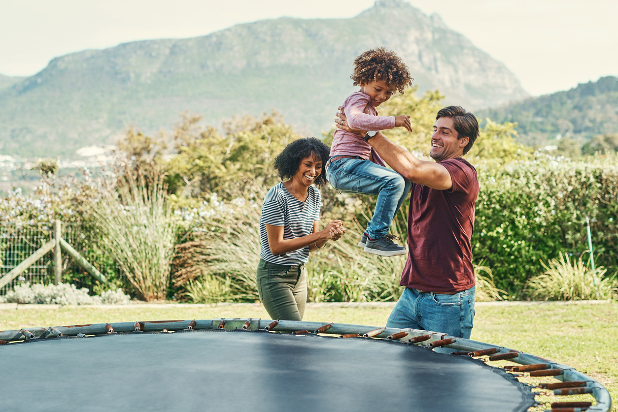 Parents playing with their child on a trampoline