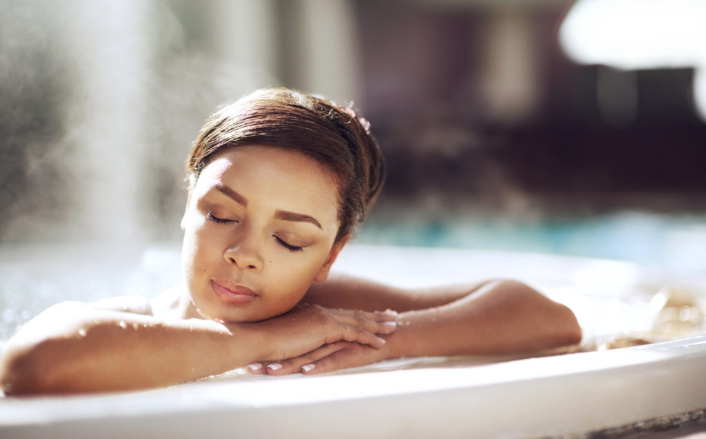 Young woman enjoying the health benefits of her hot tub.