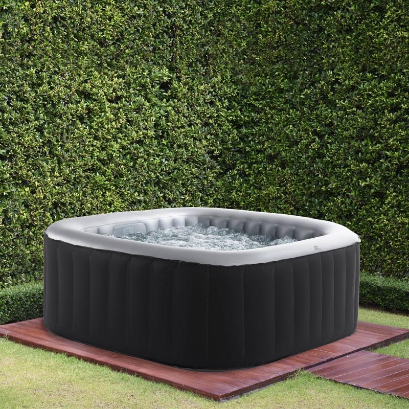 Shot of a bubbling hot tub on a garden patio.