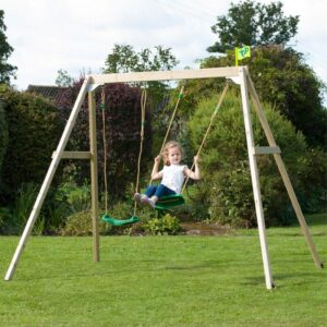 Child playing on wooden swing set